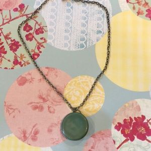 Silver necklace with jade colored round pendant.